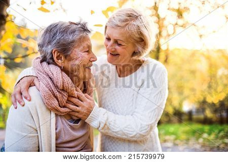 Senior women on a walk in autumn nature. An elderly woman with her senior daughter walking outside.