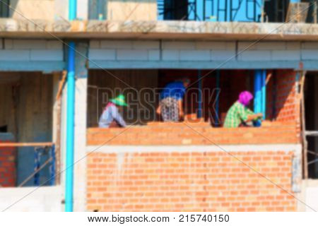 blur of female worker bricklayer laying brick a wall construction in industrial building site