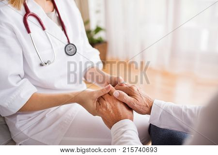 Unrecognizable health visitor and a senior man during home visit. A nurse holding hands of a man.