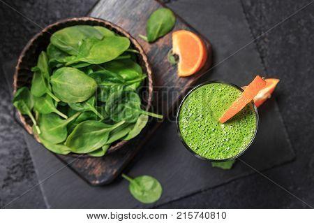 Helthy fresh Spinach smoothie with orange on black backgraund