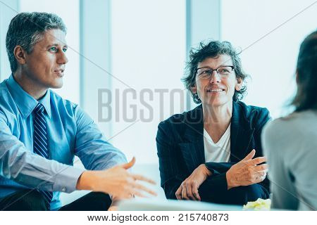 Closeup of three diverse business people discussing issues and sitting in lounge with big window in background. One woman is seen partly.