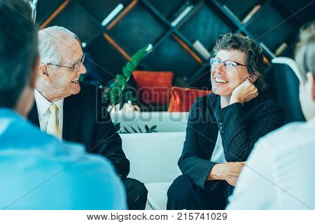Closeup of four diverse business people discussing ideas and sitting around table in lounge with blurred interior view in background. Two men are sitting back to camera.