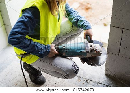 Unrecognizable female worker on the construction site. Beautiful young woman working with electric tool.