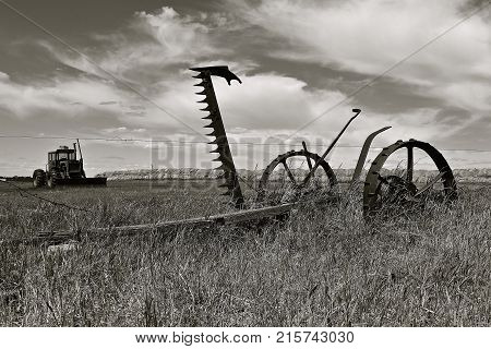 An old horse pulled hay mower with sickle bar upright and tractor and round bales in the background. (black and white)