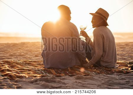 Romantic young African couple sitting together on a sandy beach at dusk toasting each other with wine