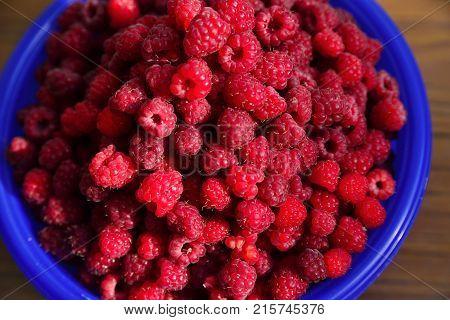 Cupful of ripe juicy raspberries on the table