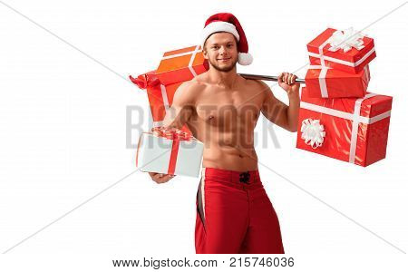 Brought you a present. Portrait of a fit shirtless man wearing Christmas hat carrying a barbell giving a present box to a viewer isolated on white, 2018, 2019.
