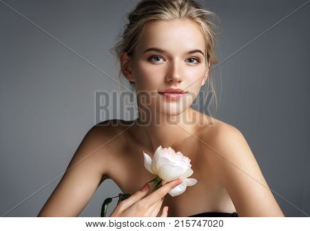 Beautiful young lady with natural make up. Photo of blonde girl with rose on grey background. Skin care concept