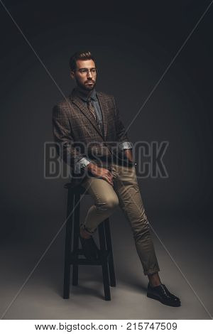 Sophisticated Man In Suit Sitting On Stool