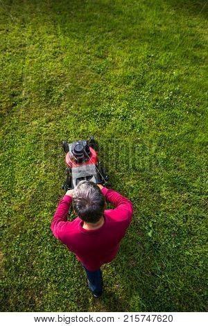 Senior man mowing the lawn in his garden