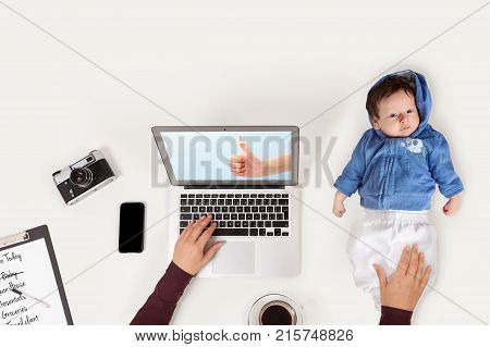 Mother holding baby while working on laptop in office. Business and family balance. Workplace with baby laptop phone and to do list from above.