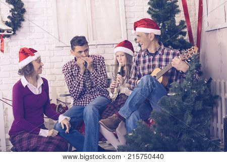Happy Family Singing In Front Of A Christmas Tree