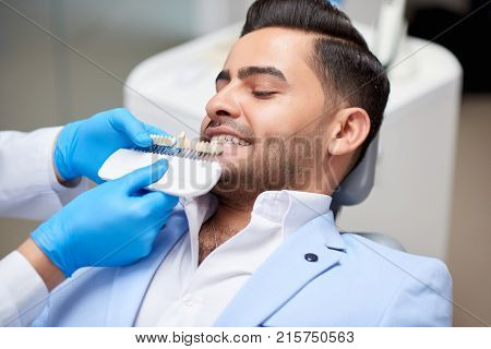 Shot of a handsome young man on a medical appointment at the dentist office professional dentist holding dentures comparing color and shade of teeth medicine healthcare whitening.