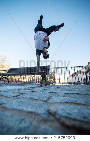 Young man doing handstand on a bench in the street while doing parkour.