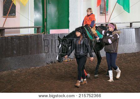 Gomel, Belarus - November 25, 2017: Horse Riding Equestrian Sport. Children Learn Horseback Riding.