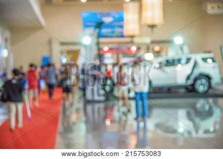 Blurred image of a people walking in motor show for background usage. Concept of business social gathering for meeting exchange.