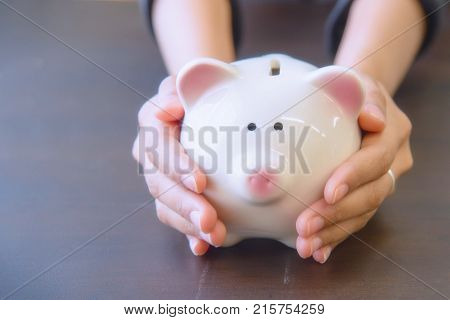 Piggy bank in hand on wooden top table money savings concept.