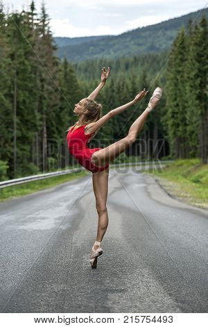 Pretty ballerina stands on the right toe on the roadway on the coniferous forest background. Her arms and the left leg outstretched upwards. She wears a red leotard and light pointes. Vertical.