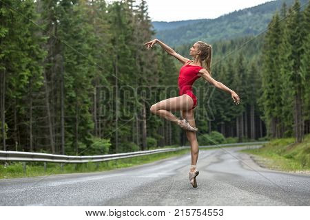 Charming ballerina stands on the right toe on the roadway on the coniferous forest background. Her arms outstretched to the sides, left leg bent in the knee. She wears a red leotard and light pointes.