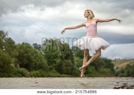 Delightful ballerina jumping in the shallow river on the background of green shore and cloudy sky. She wears white tutu, pink leotard and beige pointes. Water splashes spreading around her legs.