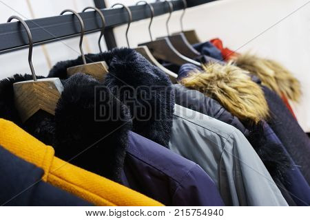 Modern outerwear in a shop on a hanger. Jackets, parks and warm outerwear of different colors and denim for youth. Outerwear of different styles on the hanger in the showroom. Soft focus.