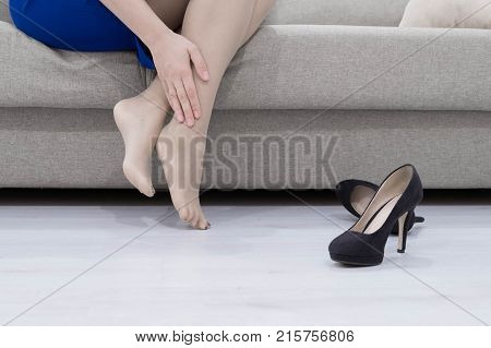 Young woman suffering from legs pain because of uncomfortable shoes, high heels.