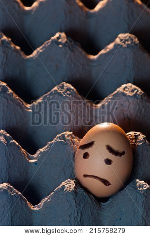 Vertical image of an egg with a sad face painted on it alone in a cardboard egg tray