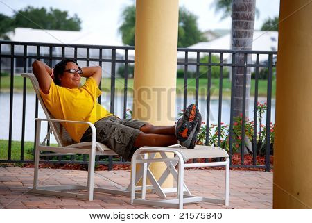 Hispanic man relaxing by a pool