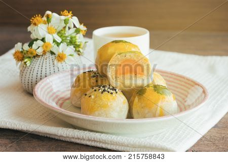Delicious Chinese pastry or moon cake filled with mung bean paste and salted egg yolk on ceramic plate. Chinese pastry served with tea on wood table in side view close up with copy space. Homemade bakery concept of moon cake or Chinese pastry.