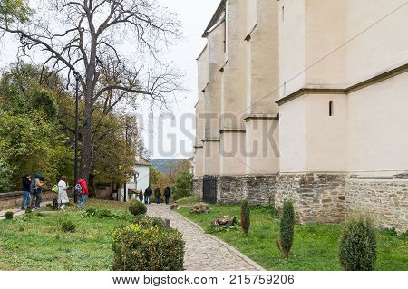 Sighisoara Romania October 08 2017 : Tourists walk around the Church of the Deal (St. Nicholas) and inspect it in the castle in Old City. Sighisoara city in Romania