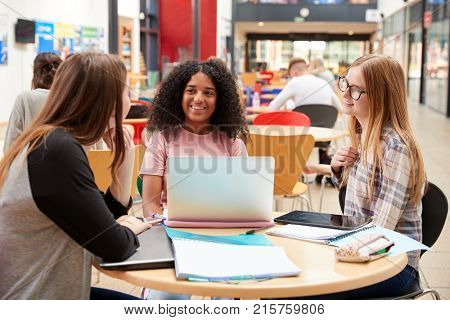 Female Students Working In Communal Area Of Busy College Campus