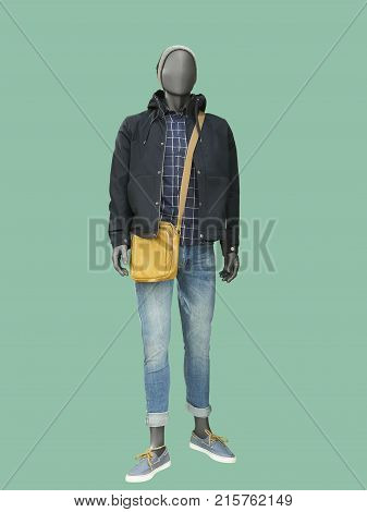 Full-length male mannequin dressed in warm jacket and blue jeans over green background. No brand names or copyright objects.