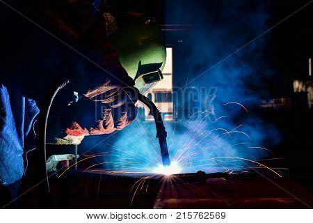 Industrial welder welding fabricated construction in factory Welding process by Flux Core Welding FCAW