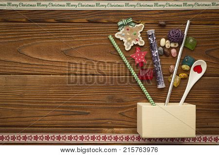 A beige box, gingerbread, straws with Christmas pattern and a porcelian teaspoon on a rustic wooden table. A star patterned ribbon on the bottom. A Merry Cristmas inscription ribbon at the top. Christmas background. Copy space. Top view