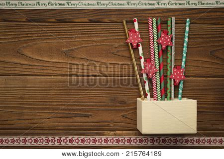A beige box, red and green straws with Christmas pattern, red stars. A star patterned ribbon on the bottom. A Merry Cristmas inscription ribbon at the top. Christmas background. Copy space. Top view