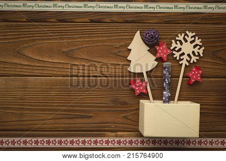 A beige box, gingerbread, wooden Cristmas toys, purple glitter in a flask. A star patterned ribbon on the bottom. A Merry Cristmas inscription ribbon at the top. Christmas background. Copy space. Top view
