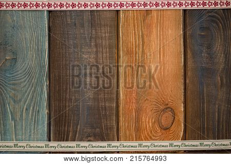 A colored wooden Christmas background. A star patterned ribbon at the top. A Merry Cristmas inscription ribbon on the bottom. Copy space. Top view