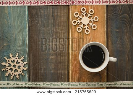 A colored wooden Christmas background with a cup of coffee, wooden snowflakes. A star patterned ribbon at the top. A Merry Cristmas inscription ribbon on the bottom. Copy space. Top view