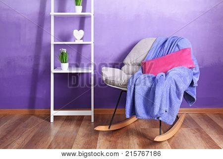 Stylish rocking armchair and shelving unit against violet wall