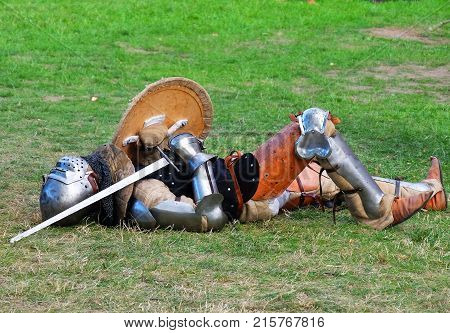 A knight lying on the grass tired or injured after a fight.