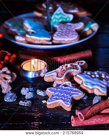Candle light table with Christmas gingerbread cookies and cinnamon stick and star sweets are on decoration tiered cake stand wooden table and burning candles. Gingerbread trees lay on table.
