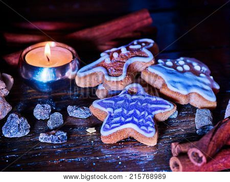 Candle light table with Christmas gingerbread cookies and cinnamon stick and star sweets are on wooden table and burning candles. Xmas still life object. Close-up.