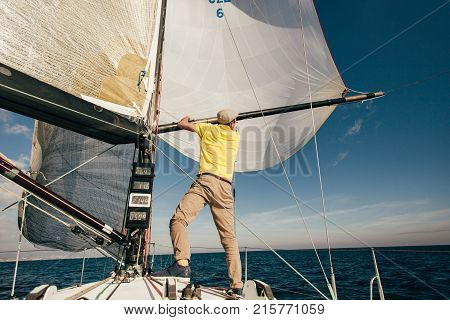 Professional sailor or yachtsman uses mast and forestay to put up spinnaker or mainsail on racing competition yacht or sailboat on warm summer day