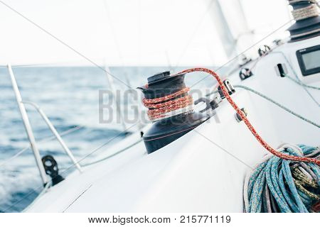 Racing yacht or professional sailboat leaning to side pushed by water and wind in spinnaker and mainsail sailors attach ropes and nautical knots to winch