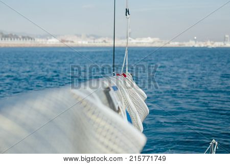 Professional sailor or specialist in regatta yachts or sailboat competition attaches spinnaker sail or mainsail on racing boat in open sea or ocean on sunny day expensive hobby