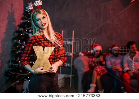 Christmas, x-mas, New year, winter, happiness concept - smiling woman in santa helper hat with a wooden letter X. Funny people. Christmas party at home