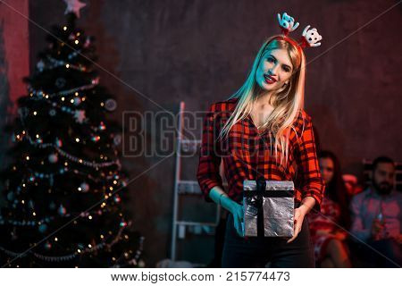 Christmas, x-mas, New year, winter, happiness concept - smiling woman in santa helper hat with gift box. Funny people. Christmas party at home