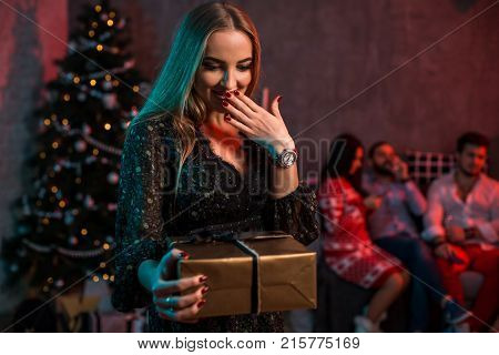 Christmas, x-mas, New year, winter, happiness concept - smiling woman with gift box. Funny people. Christmas party at home