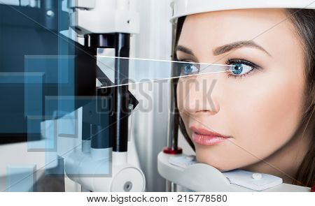 Woman checking eyesight in a clinic using diagnostic ophthalmic device .virtual laser Ray directing for checking vision, Future technology