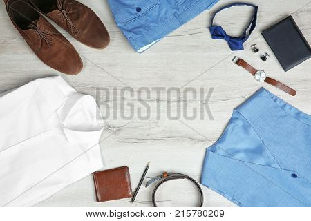 Male clothes, footwear and accessories on wooden background